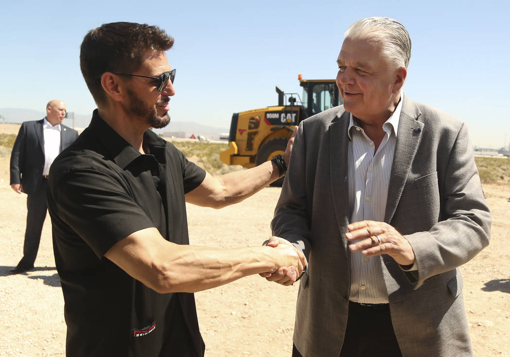 Switch CEO Rob Roy, left, shakes hands with Nevada Gov. Steve Sisolak during a ceremonial groun ...