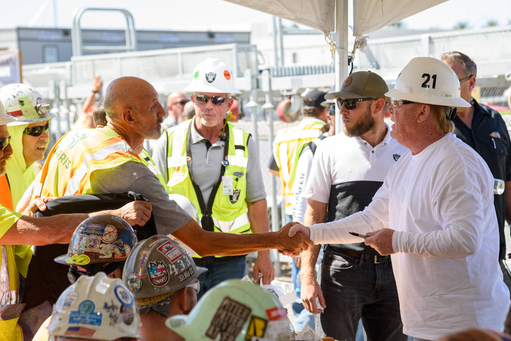 Raiders owner Mark Davis shakes hands with a construction worker during a lunch prepared by Lev ...