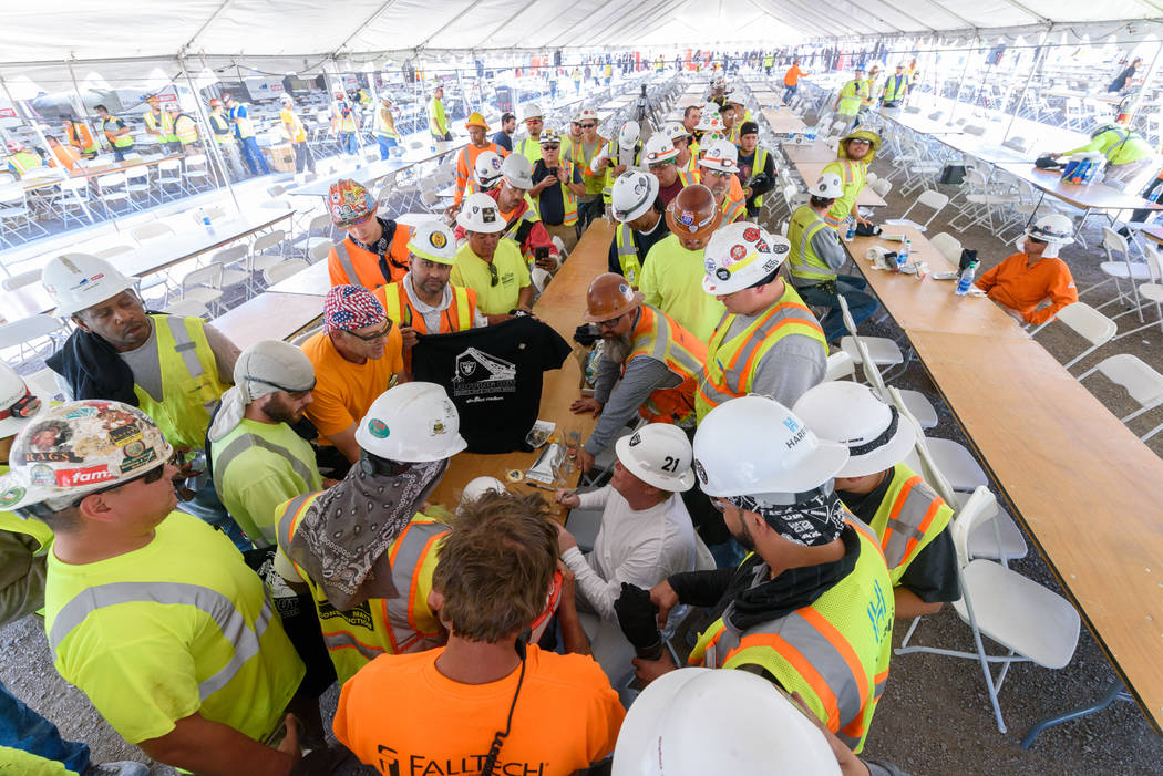 Raiders owner Mark Davis signs memorabilia for construction workers during a lunch prepared by ...