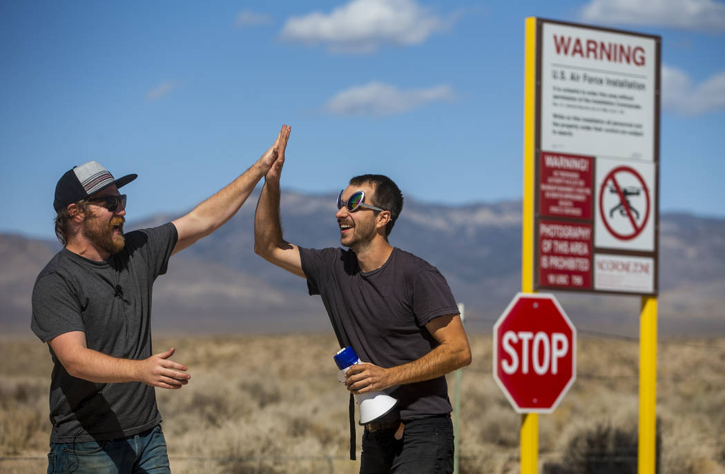 Devin Caldarone, left, and Mike Dye of Los Angeles celebrate their pretend crossing into Area 5 ...