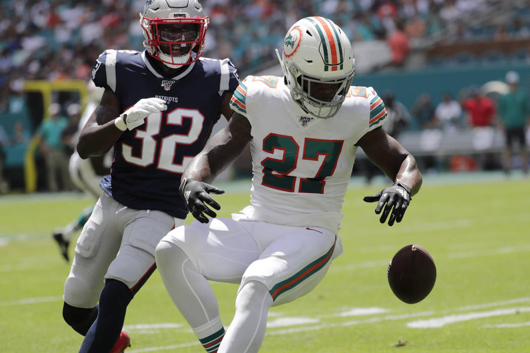 Miami Dolphins running back Kalen Ballage (27) drops a pass under pressure from New England Pat ...