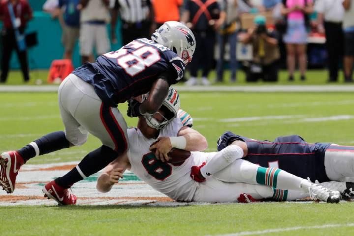 New England Patriots outside linebackers Jamie Collins (58) and Elandon Roberts (52) sack Miami ...