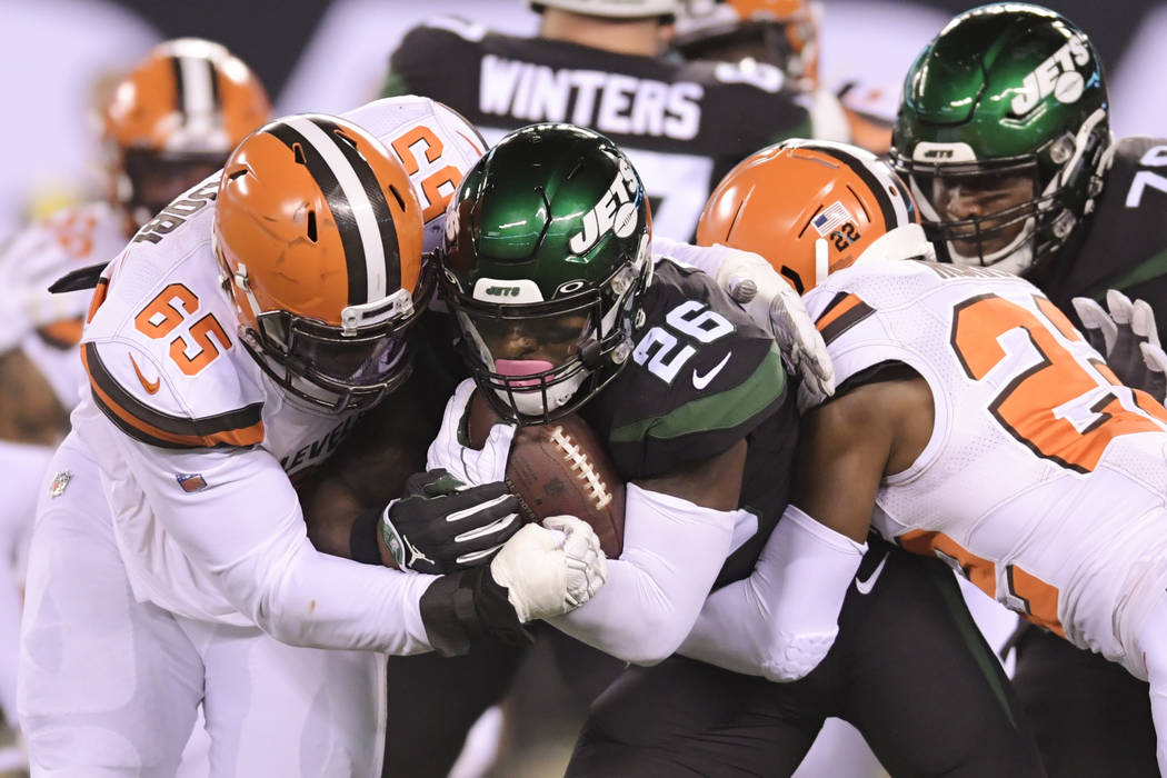 Cleveland Browns' Larry Ogunjobi (65) and Eric Murray (22) tackle New York Jets' Le'Veon Bell ( ...