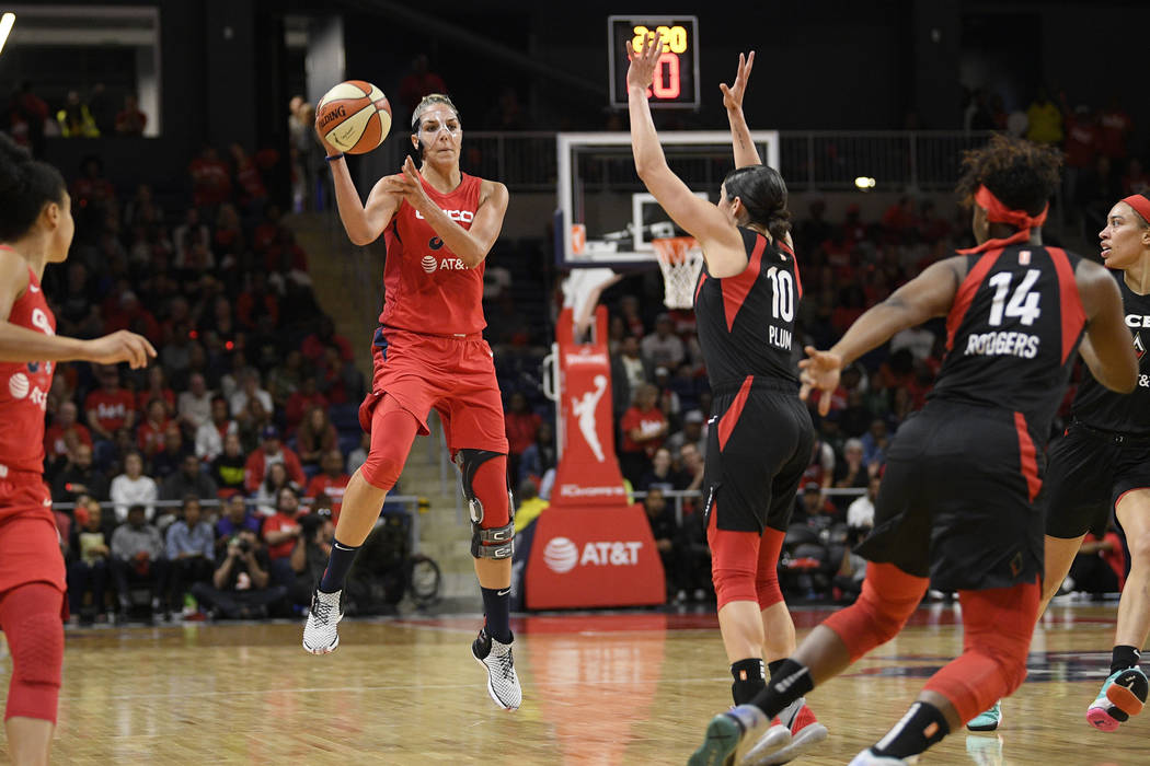 Washington Mystics forward Elena Delle Donne, left, jumps up to pass the ball as Las Vegas Aces ...