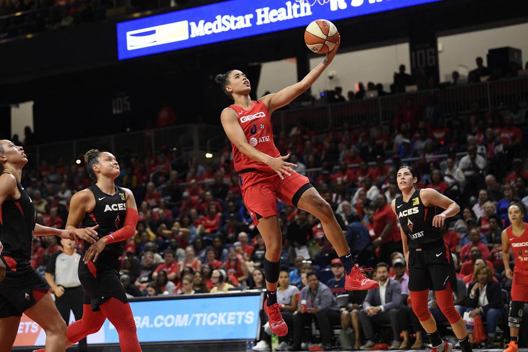 Washington Mystics guard Natasha Cloud, center, goes to the basket between Las Vegas Aces guard ...