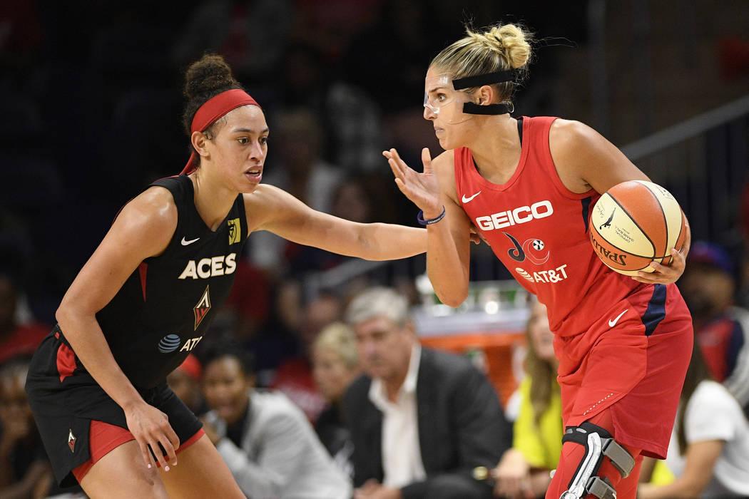 Washington Mystics forward Elena Delle Donne, right, handles the ball as Las Vegas Aces forward ...