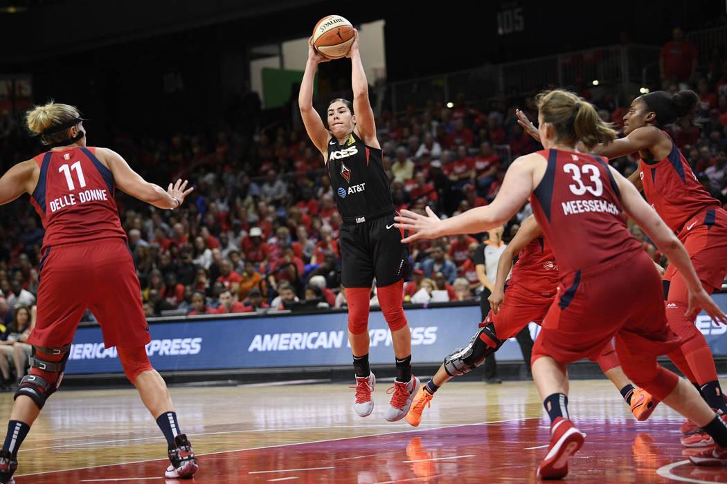Las Vegas Aces guard Kelsey Plum, center, jumps up to pass the ball as Washington Mystics forwa ...