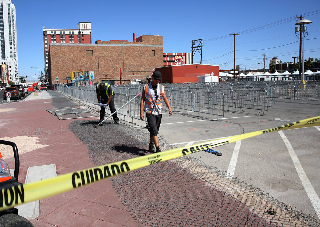 Workers put up temporary fences at the corner of Carson Avenue and Seventh Street in preparatio ...