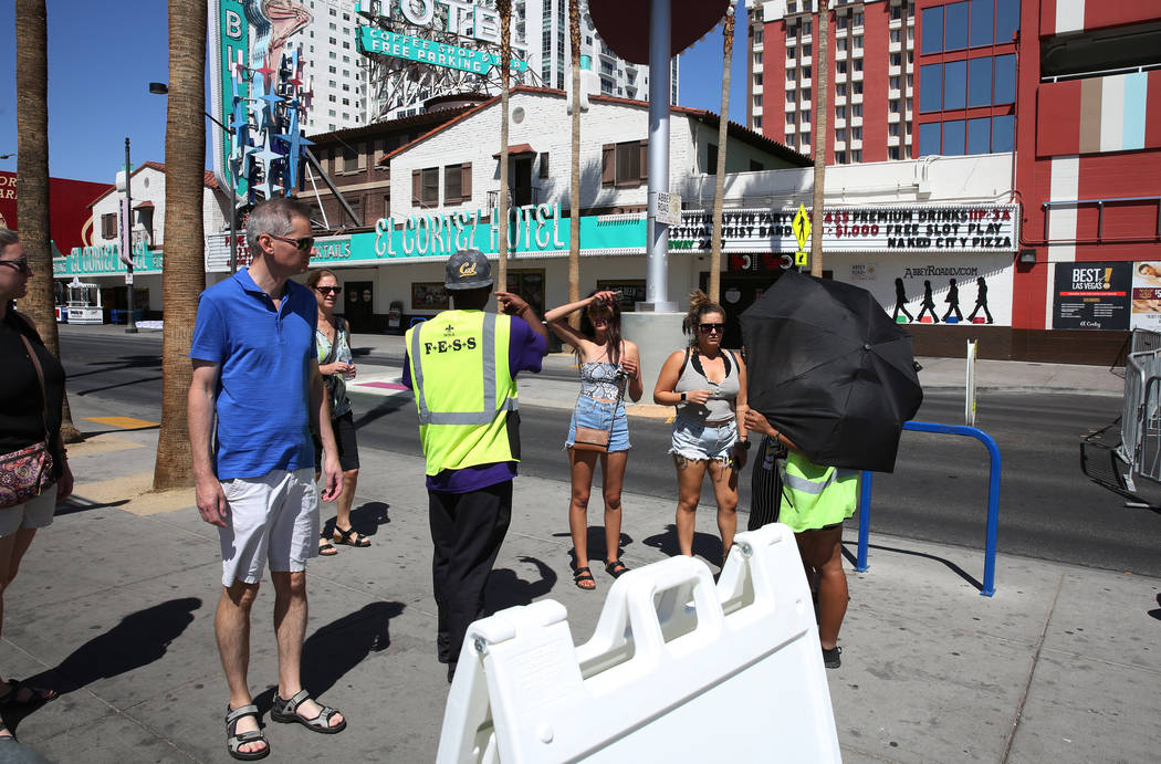 Security guards stop pedestrians to let them know that Fremont Street is closed for pedestrian ...