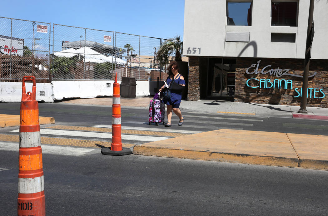 A guest at El Cortez Cabana Suites navigates through Ogden Street where the street is closed fo ...