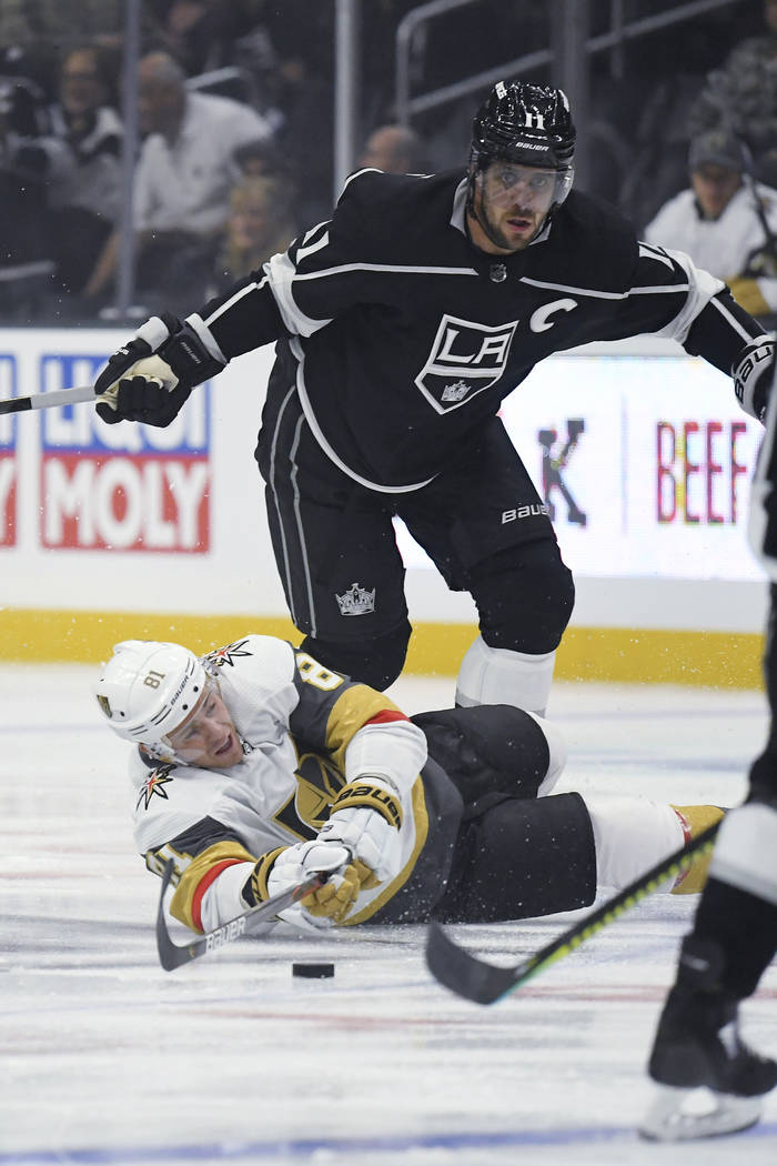 Vegas Golden Knights center Jonathan Marchessault, below, falls as he passes the puck while und ...