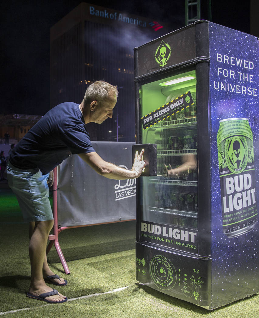 Sean Marcoux tries to unlock a case of special alien edition Bud Light during the Area 51 Celeb ...
