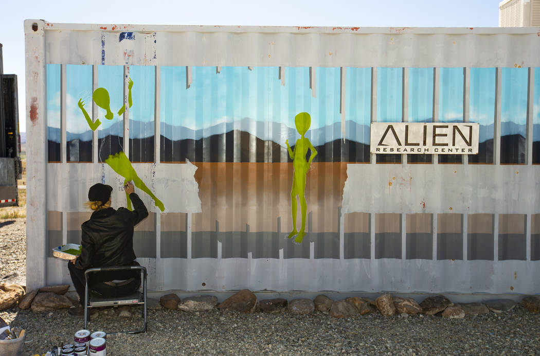 Artist Brandy Whisenant continues to paint a mural on the side of a container about the Area 51 ...