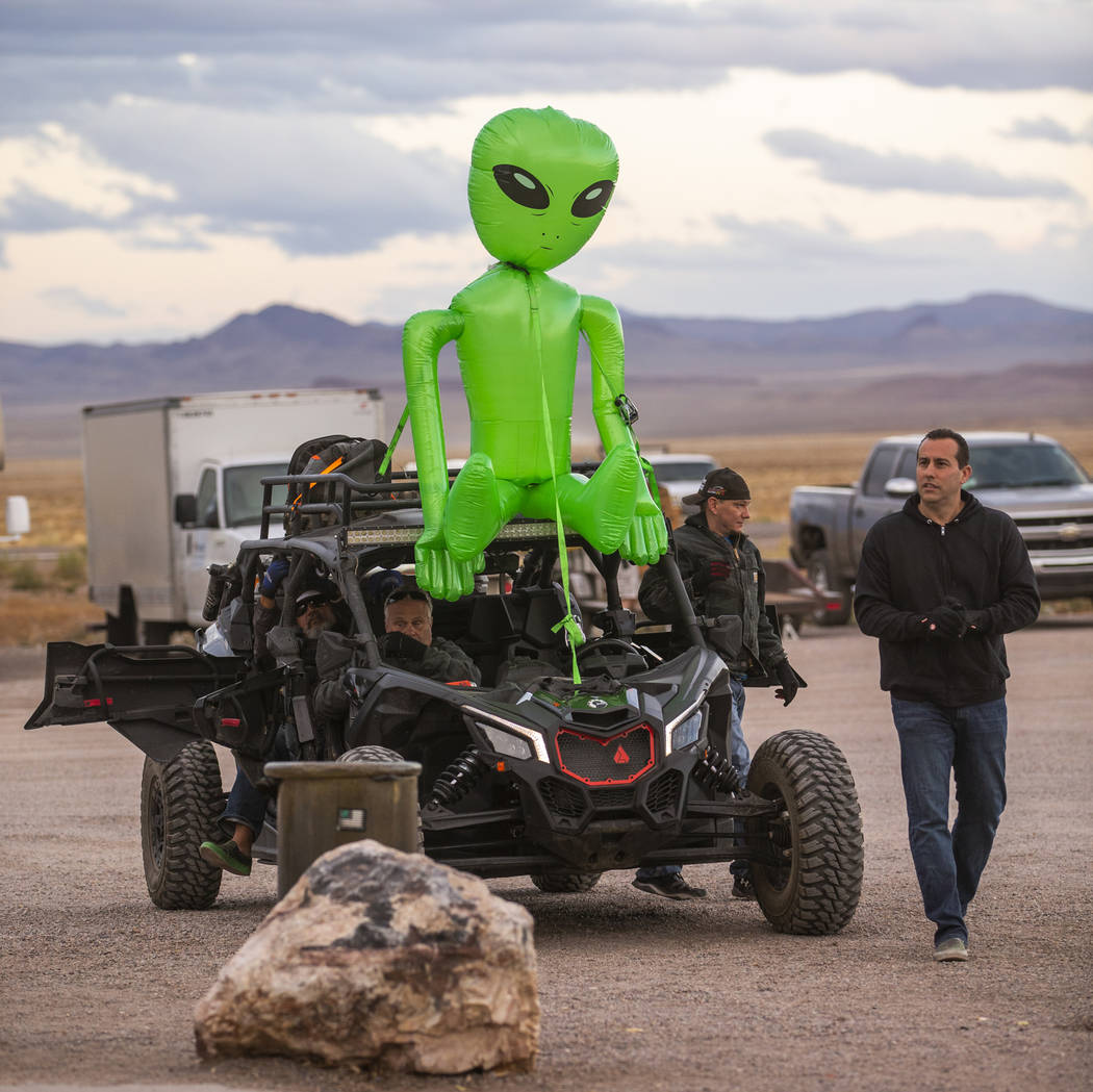 Festivalgoers arrive by all-terrain vehicle with an alien strapped to the top in front of the L ...
