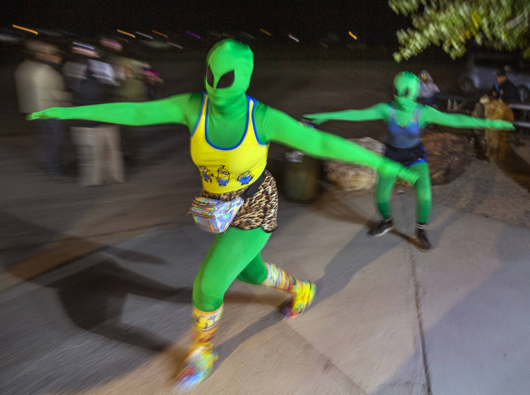 A pair of aliens move about festivalgoers at the Little A'Le'Inn late on the first night of Ali ...
