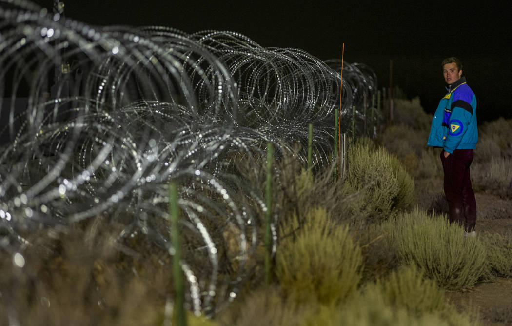 Michael Fortner of Cincinnati wanders along the fence line near the back gate of Area 51 in ho ...