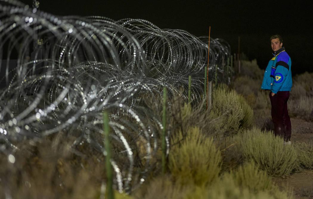 Michael Fortner of Cincinnati wanders along the fence line near the back gate of Area 51 in ho ...