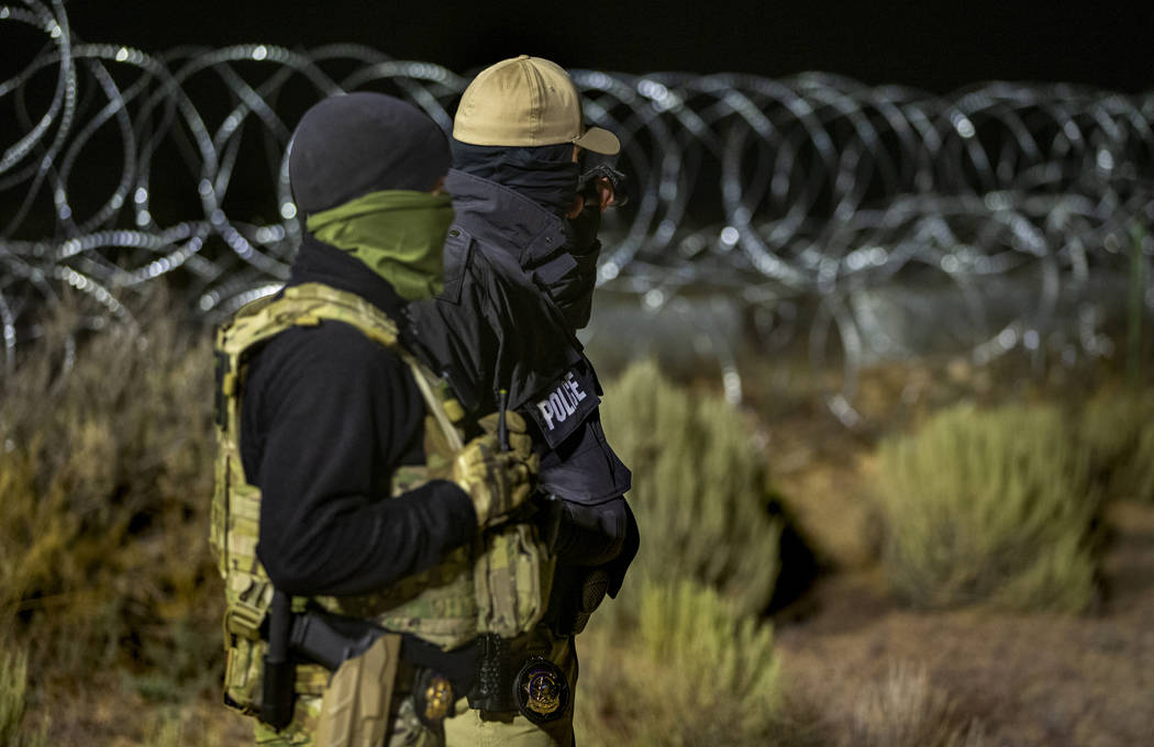 Security personnel stand along the fence line near the back gate of Area 51 in homage to the or ...