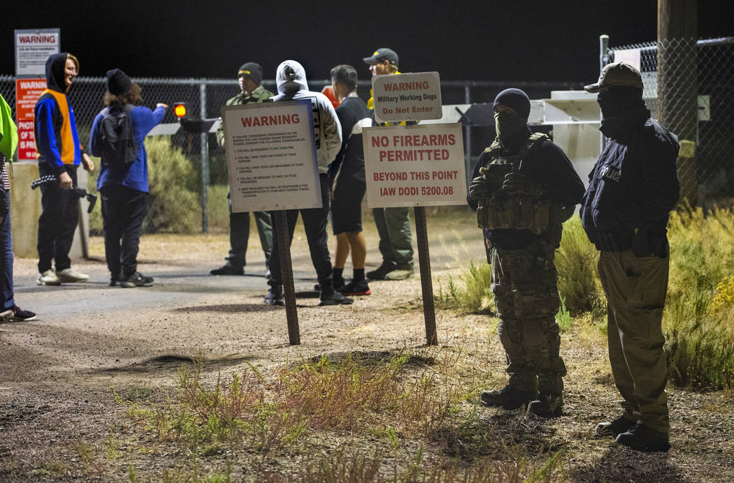 Security personnel and attendees stand along the fence line near the back gate of Area 51 in ho ...