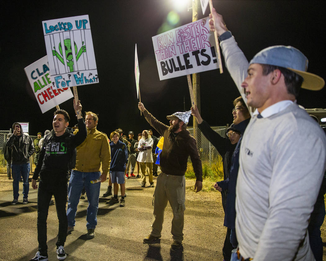 Individuals chant with signs in hand outside the back gate of Area 51 in homage to the original ...