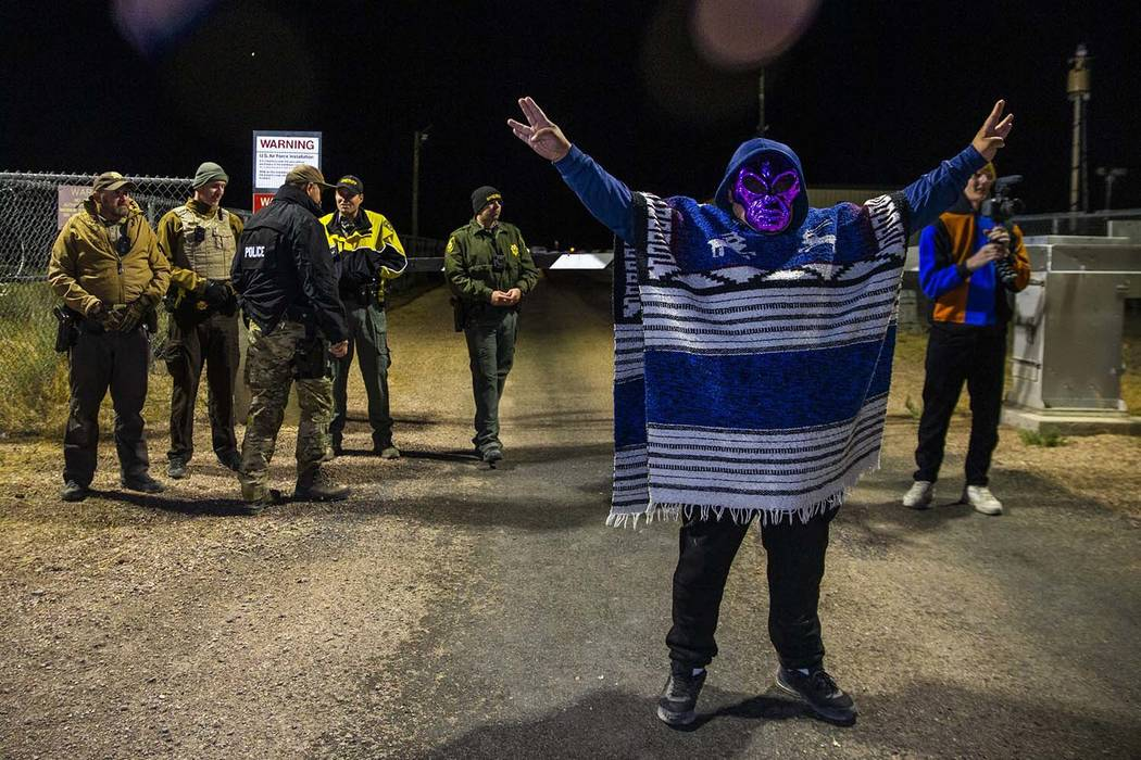 A masked individual arrives at the Area 51 back gate and stands before security personnel to pa ...