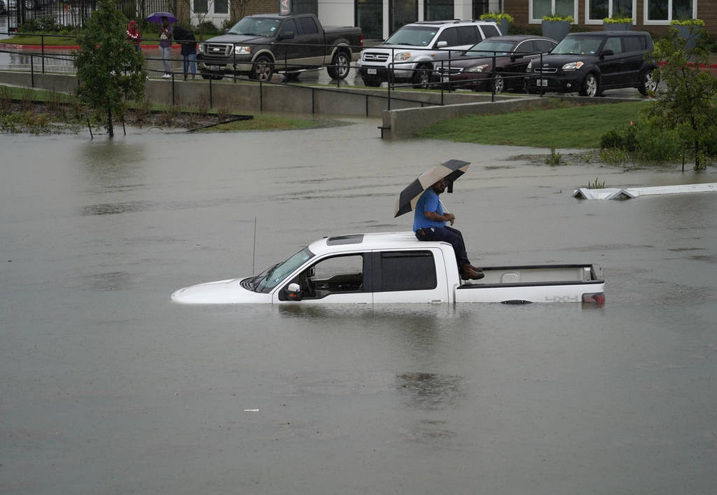 A man sits on top of a truck on a flooded road, Thursday, Sept. 19, 2019, in Houston. Members o ...