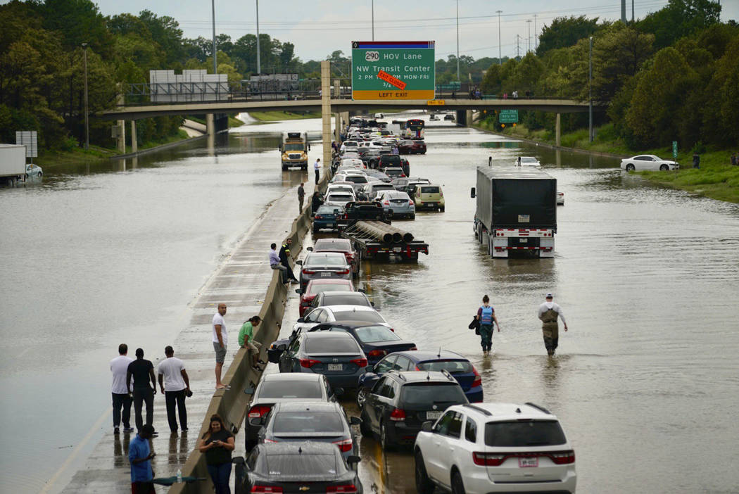 People wait outside of their stranded vehicles along Interstate 10 westbound at T.C Jester, Thu ...