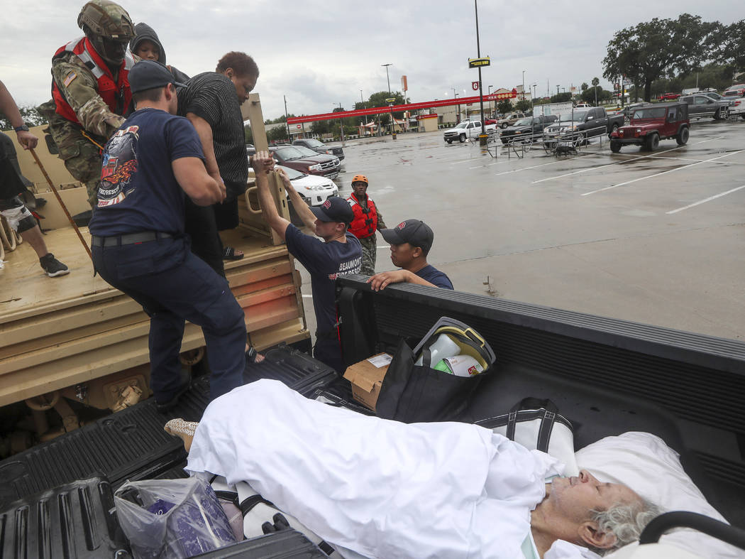 Dwain Kaufman, right, waits for his wife as she is helped into the back of a family member's tr ...