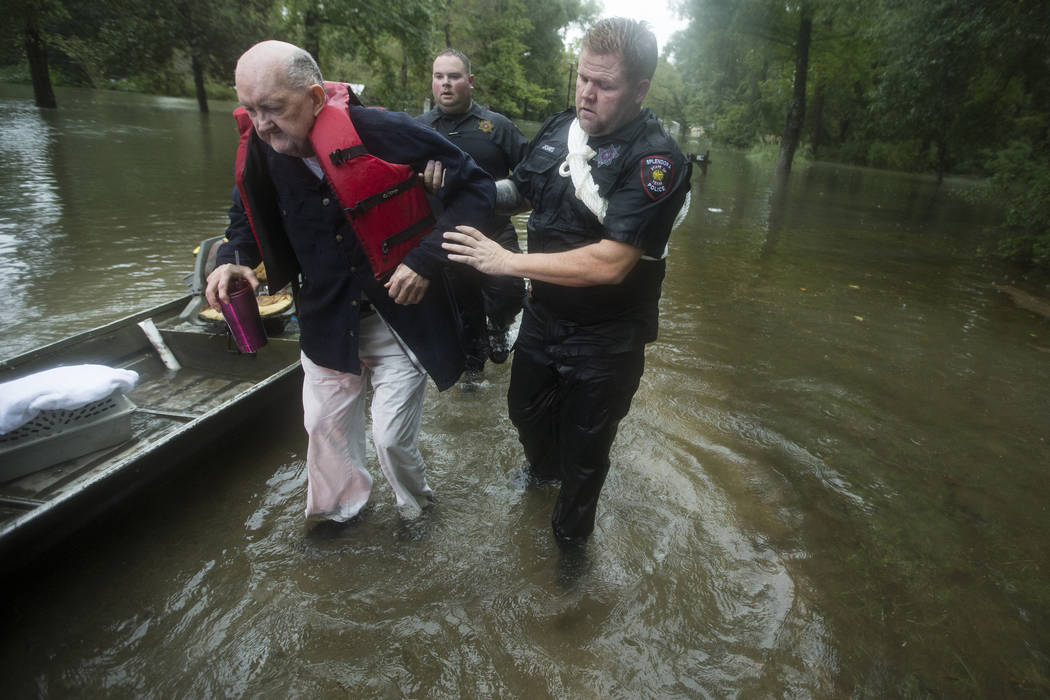 Fred Stewart, left, is helped to high ground by Splendora Police officer Mike Jones after he wa ...