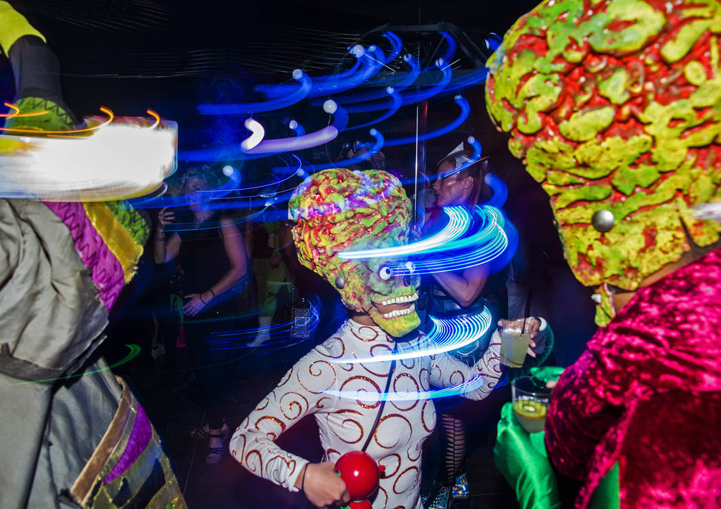 """Attendees dressed as characters from the movie """"Mars Attacks!"""" dance during a pre-party for Sto ..."""