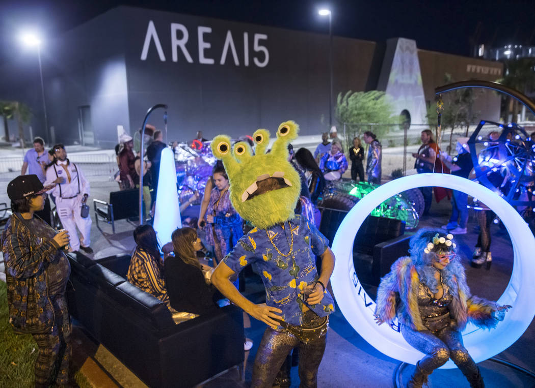 Alien-themed party goers socialize outside during a pre-party for Storm Area 51 on Thursday, Se ...