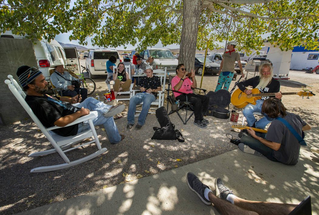 Festivalgoers relax and enjoy some music under the tree at the Little A'Le'Inn during the Alien ...