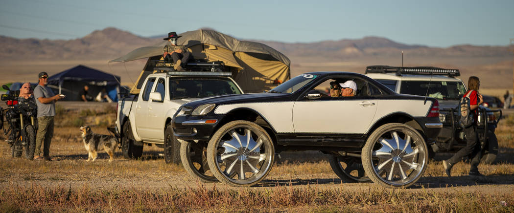 A custom vehicle cruises past festivalgoers parked on the frontage road during the Alienstock f ...