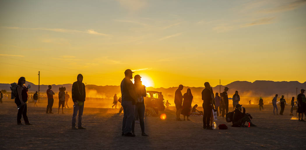 The sun sets on the second day as festivalgoers enjoy music from the main stage during the Alie ...
