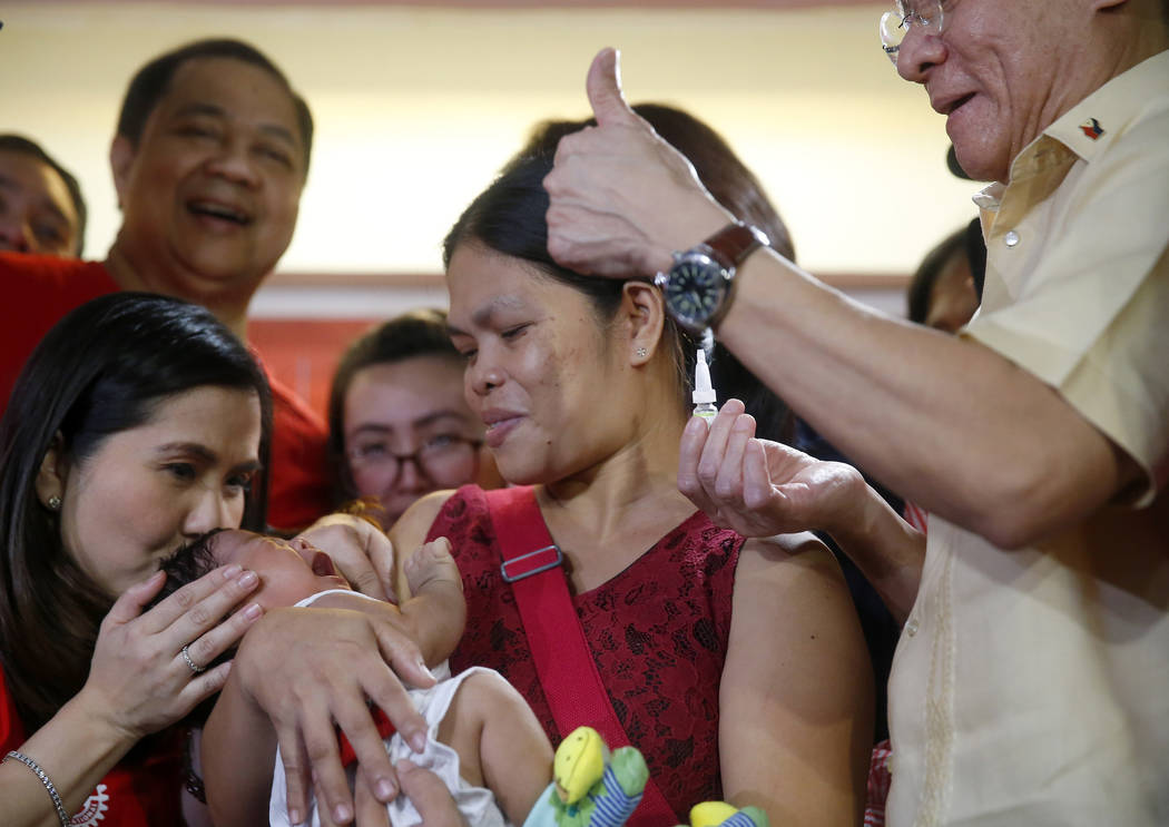 Philippine Health Secretary Francisco Duque III, right, flashes the thumbs up sign shortly afte ...
