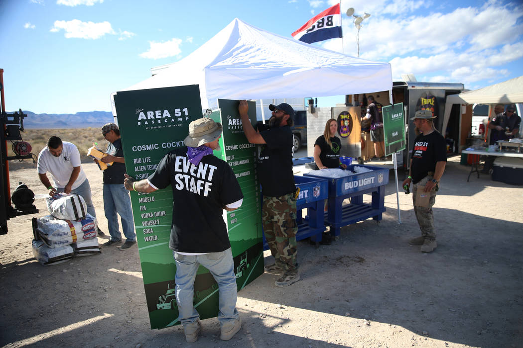 Staff members set up signs during the Alien Basecamp alien festival at the Alien Research Cente ...