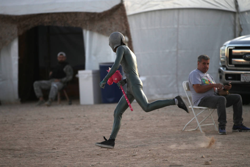 A person runs wearing an alien costume during the Alien Basecamp alien festival at the Alien Re ...