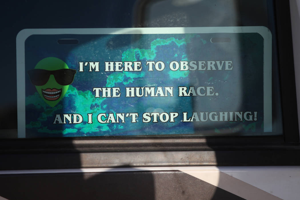 A sign inside a vehicle parked parked outside oft the Alien Basecamp alien festival at the Alie ...