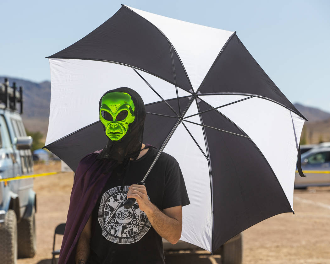 Another alien stays cool while walking over to the Little A'Le'Inn from parking during the Alie ...