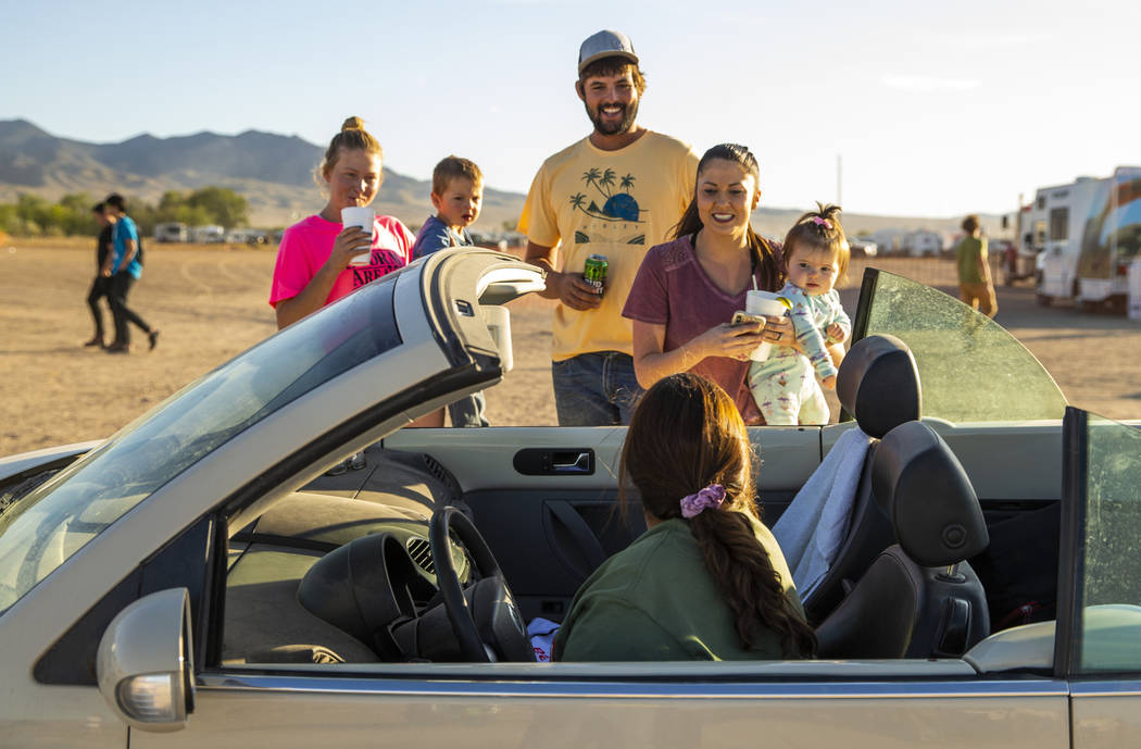 Friends stop and chat with Connie West, in car, of the Little A'Le'Inn during the Alienstock fe ...