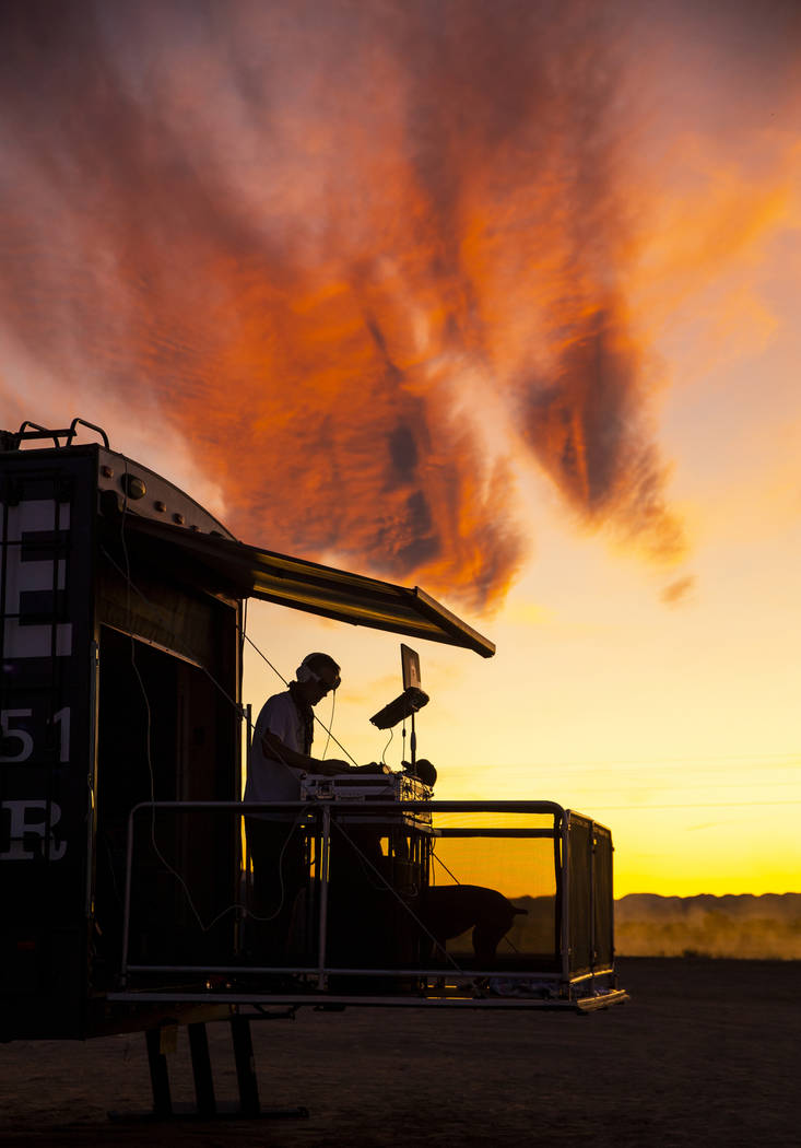 DJ Karn Elofson of Sweden plays into the sunset on his own small stage off of the festival grou ...
