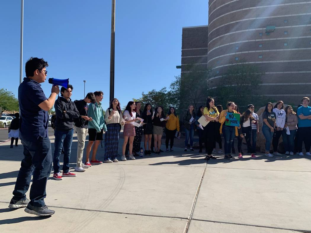 Palo Verde High School senior Dexter Lim, left, leads his peers in a chant during a global clim ...