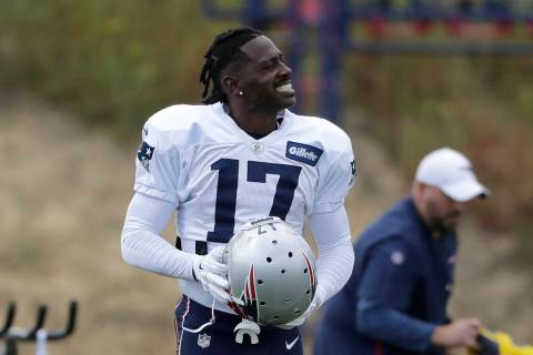 New England Patriots wide receiver Antonio Brown carries his helmet during an NFL football prac ...