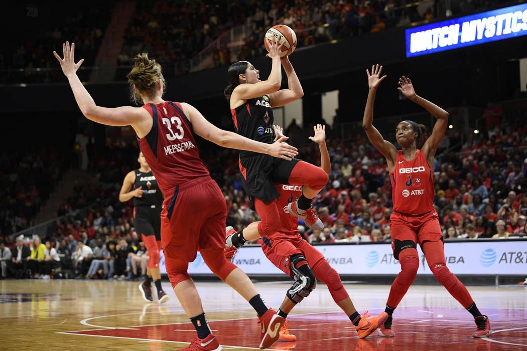 Las Vegas Aces guard Kelsey Plum, center, goes to the basket against Washington Mystics center ...