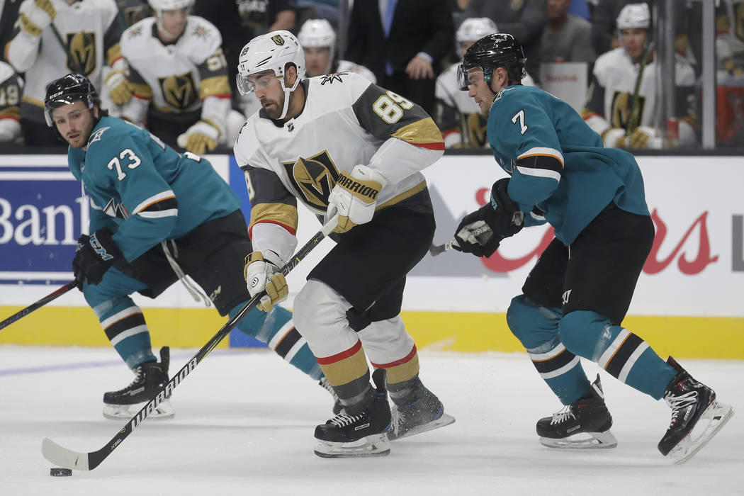 Vegas Golden Knights right wing Alex Tuch (89) skates between San Jose Sharks centers Noah Greg ...