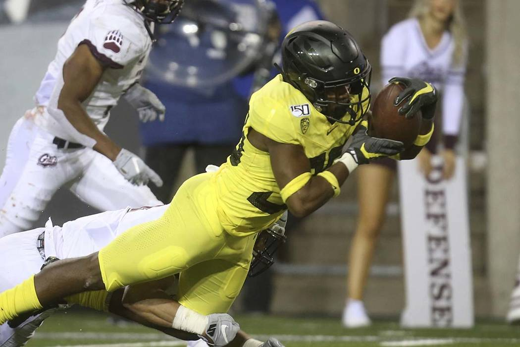 Oregon's Jaylon Redd, right, dives into the end zone for a touchdown against Montana during the ...