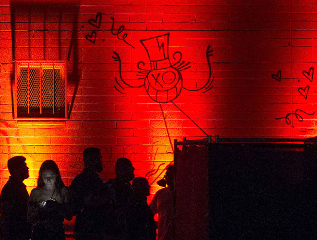 Attendees walk through an illuminated walkway during the first day of the Life is Beautiful fes ...