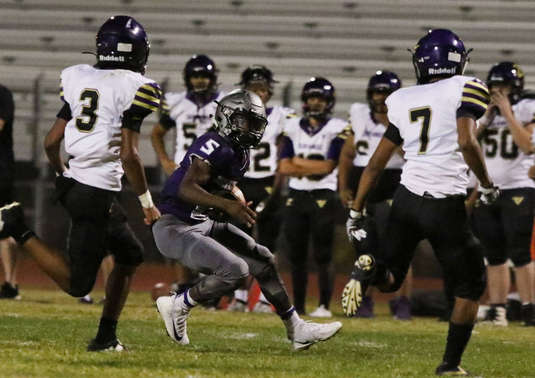 Silverado High's running back Jacob Mendez, center, surrounded by Durango High defense during t ...