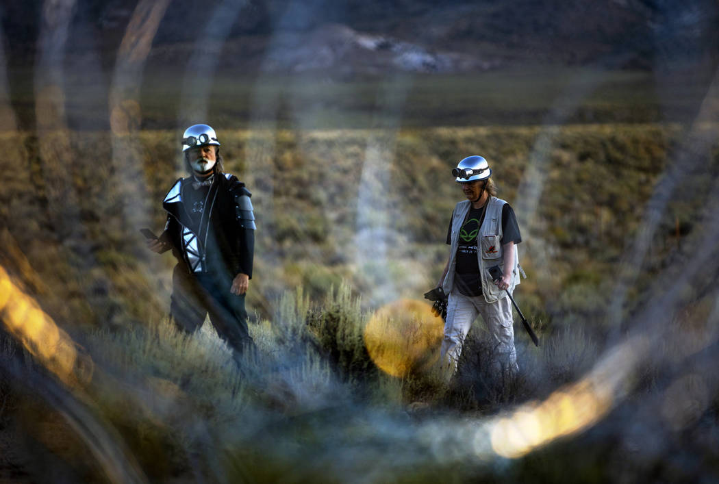 Matthew Devlen and Kim Dillinger Davis walk along the fence line with razor wire at the back ga ...