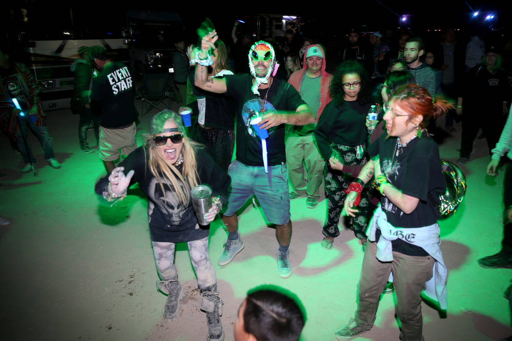 People dance during a performance by Grammy-nominated DJ Paul Oakenfold during the Alien Baseca ...